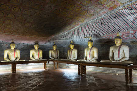 Group of sitting Buddha statues in cave buddhist temple with bright painted murals on walls and ceiling  in Dambulla Golden temple in Sri Lanka