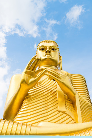 Big golden Buddha statue in wheel-turning pose on the top of a building with blue sky on background Stock Photo