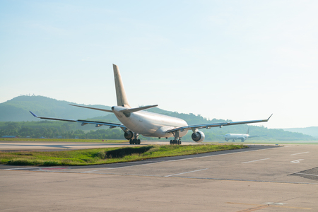 Big passenger airplanes on runway strip are taxiing for take-off Фото со стока