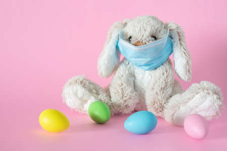Easter stuffed toy bunny in protective face mask and colored eggs on pink background. Ester holiday during pandemic concept.