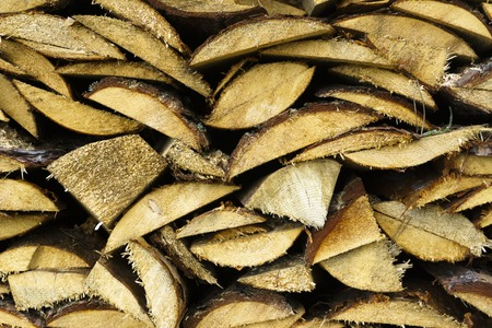 Logs of firewood piled under the roof of slate. Fuel for stove heating. Country life. Wooden firewood stacked wall. Natural wood background. Firewood stacked in several rows. Banco de Imagens