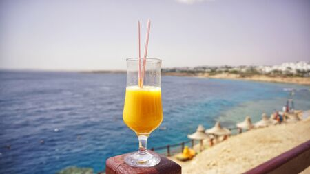 glass of fresh mango on the table on sea background