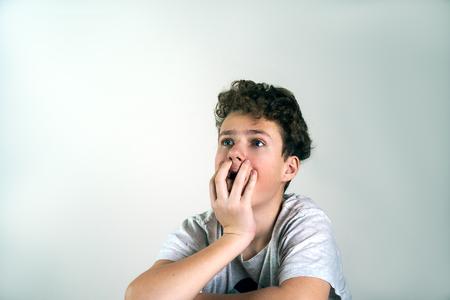 Portret van bange jongen zit op bruine stoel op grijze achtergrond. Adolescent, tiener.
