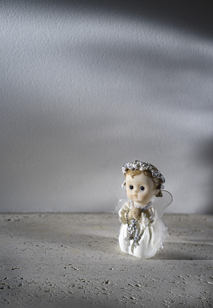 Close up beautiful little angel with white wings standing with your arms close to your chest as in prayeris in rays of light on gray background. Close up. Christmas decoration card concept. Banque d'images