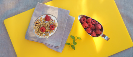Top view healthy breakfast with glass homemade granola with yogurt and fresh berries raspberries in silver bowl fresh orange juice mint gray kitchen cloth napkin on yellow background. Selective focus Stock Photo