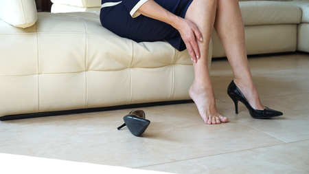Business woman touching feet with her hand. Cropped image of woman in black high heels massaging her tired legs. Varicose veins concept. Painful varicose and spider veins on female legs.