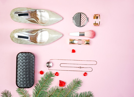 Fashion woman accessories outfit set gold heels jewelry clutch makeup cosmetic brushes fir tree pastel pink background. Flat lay top view copy space. Christmas New Year party cocktail conception.