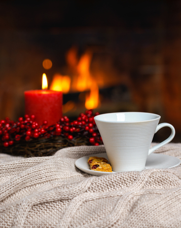 Cup of hot drink with cookie berries and red candle in red Christmas decoration on cozy knitted plaid in front of fireplace. Christmas New Year concept. Cozy relaxed magical atmosphere home interior. Stock fotó