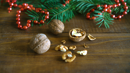 Christmas background, walnuts, shell, fir tree branch and red bead balls Christmas decoration in shape of a heart on rustic wooden table. Empty space for text, New Year theme concept.