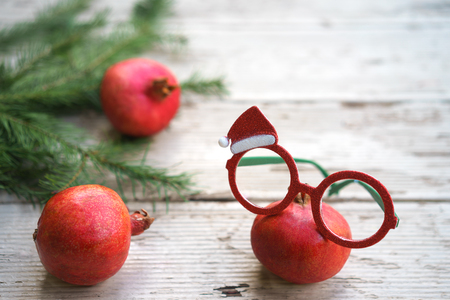 Christmas New Year layout healhy eye concept. Vivid red Christmas pomegranates spectacles glasses with holiday decorative frame and fir tree branches on rustic gray wooden background. Copy space Stock Photo