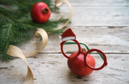 Vivid red Christmas pomegranates spectacles glasses with holiday decorative frame and fir tree branches on rustic gray wooden background. Christmas New Year layout healthy eye concept. Copy space. Stok Fotoğraf