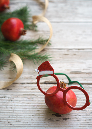 Vivid red Christmas pomegranates spectacles glasses with holiday decorative frame and fir tree branches on rustic gray wooden background. Christmas New Year layout healthy eye concept. Copy space. Stock Photo