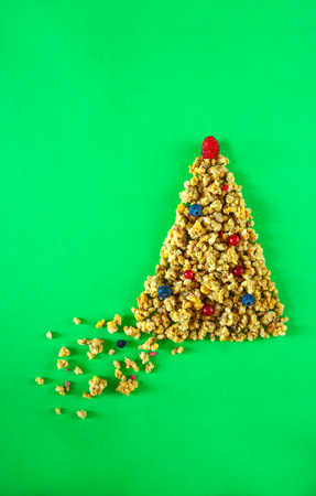 Top view granola or muesli in shape of Christmas tree with balls of berries and raspberry on top green background. Christmas healthy lifestyle layout. New Year concept for diet healthy breakfast. 스톡 콘텐츠
