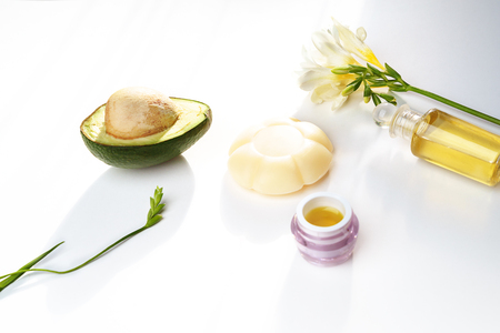 Beauty concept avocado, skin care facial essence oil, soap, lily flower box for gift and towel on white background. Facial treatment preparation for cosmetic clinic. beauty spa. copy space Stock Photo