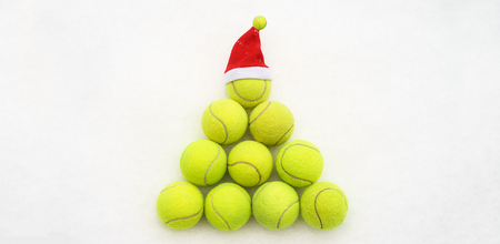 Santa hat on tennis ball on white snow background. Merry Christmas and New year concept with tennis balls. Yellow green color tennis balls in shape fir tree. Close up, sport lifestyle. Isolated, horizontal