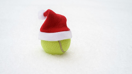 Santa hat on tennis ball on white snow winter background. Merry Christmas and New year concept with tennis balls. Close up, sport lifestyle, funny. Isolated, horizontal