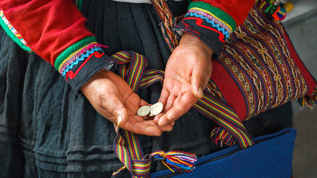 Hands of peruvian woman holding national coins metal sol. Close up of weaving and culture Peru, Cusco. woman dressed in colorful traditional native Peruvian closing in the market in Machu Picchu