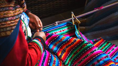 Handen van Peruaanse vrouw die alpacawoltapijt met nationaal patroonclose-up maakt. Vervaardiging van wolmateriaal in Peru, Cusco. Vrouw gekleed in kleurrijke traditionele inheemse Peruaanse sluiting