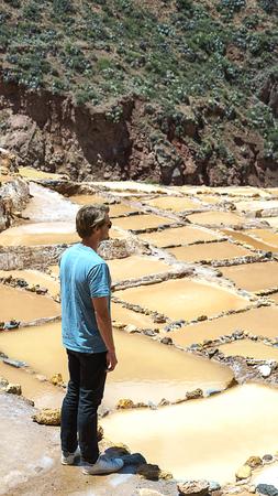 Maras, Cusco, Peru - 01.05.2019. handsome man looking at shallow pools with salt pans in Salinas de Maras Urumbamba valley in Peru, top tourist attraction in Peru, Latin America Editorial