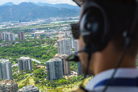 View from a helicopter cockpit flying over Rio de Janeiro, Brazil. Cockpit with pilot and control board inside the cabin in a sunny day. Selective focus, Horizontal