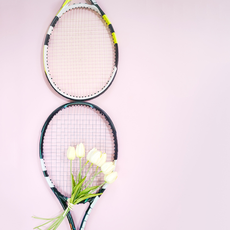 International Womens Day March 8 shape made of tennis rackets with bouquet white tulips and copy space on pastel pink background. Valentines day concept with tennis play. Flat lay, horizontal.