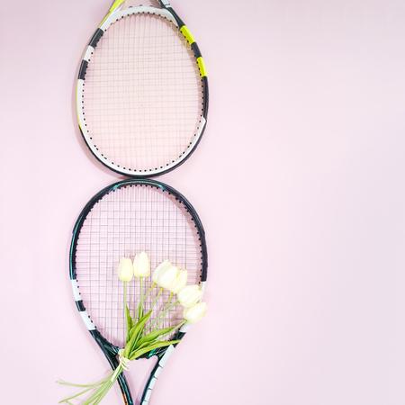 Internationaler Frauentag 8. März Form aus Tennisschlägern mit weißen Tulpen und Kopienraum auf pastellrosa Hintergrund. Valentinstag-Konzept mit Tennisspielen. Flache Lage, horizontal.