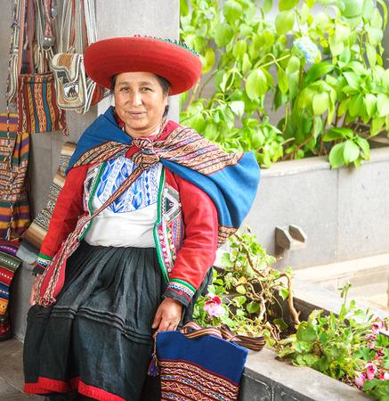 Cusco, Peru - 01.03.2019 Native Peruvian woman in traditional colorful dress with red hat in Sacred Valley near Cusco, Peru, Latin America