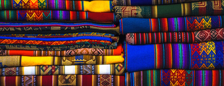 Peruvian traditional colourful native handicraft textile fabric at market in Machu Picchu