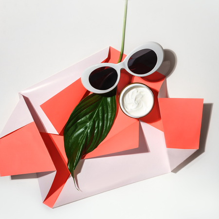 Creative layout made of green tropical leaf, sunglasses and cream on paper of living coral color on white