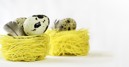 Creative layout made of easter eggs and feathers on yellow spaghetti nests on white