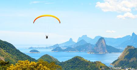 Ein bunter Fallschirm mit Fallschirmspringer am sonnigen blauen Himmel Standard-Bild