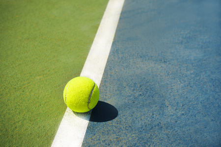 Tennis ball on a tennis court. Green and blue background field.
