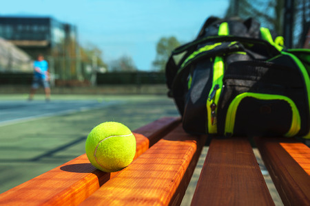 Tennis ball and sport bag on the bench on court. Concept of sport, healthy lifestyle. Stock Photo