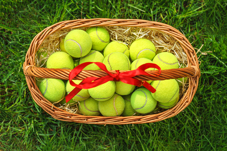 Tennis Easter with tennis balls in a basket on green grass. Selective focus, copy space, top view, flat lay.
