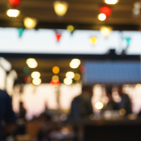 Sfocato di uomini clienti seduti al ristorante, al bar o al night club, con bokeh e lampadine luminose.