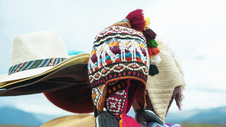 Peruvian traditional colorful handicraft textile hats with llama pattern at the market in Machu Picchu