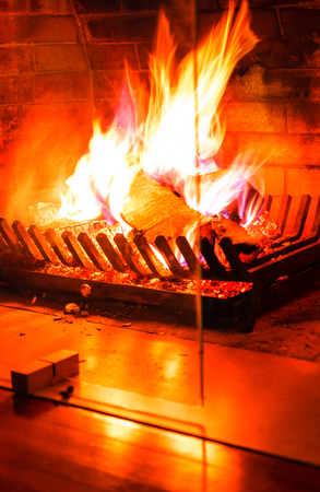 Burning fireplace. Wood burning in a cozy fireplace at home in interior. Imagens