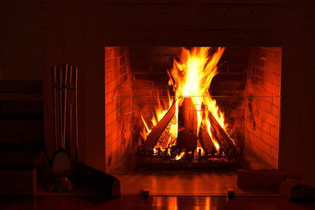 Burning fireplace. Wood burning in a cozy fireplace at home in interior. Christmas New Year winter concept decorations.