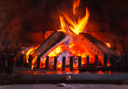 Burning fireplace. Wood burning in a cozy fireplace at home in interior. Christmas New Year winter concept decorations. Imagens