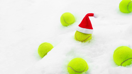 Tennis winter concept with tennis balls on white snow. Top view, copy space. Christmas New Year sport healthy layout. Santa Claus hat on the top off ball. Stock Photo