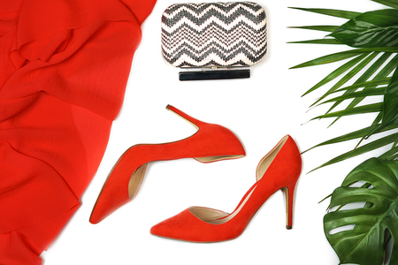 Top view party outfit red shoes accessories jewelry clutch tropical leaves on white background, isolated. Party Valentines Day Christmas Happy New Year wedding dinner set. Flat lay, copy space.