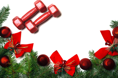 Exercise, Fitness, sport and Working Out Merry Christmas and Happy new year background with dumbbells, branches fir tree glass balls and bows bells on white background. Copy space. Flat lay, top view. Stock Photo