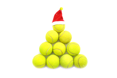 Santa hat on tennis ball on white snow background. Merry Christmas and New year concept with tennis balls. Yellow green color tennis balls in shape fir tree. Close up, sport lifestyle. Isolated.