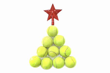 Red star on tennis ball on white snow background. Merry Christmas and New year concept with tennis balls. Yellow green color tennis balls in shape fir tree. Close up, sport lifestyle. Isolated.