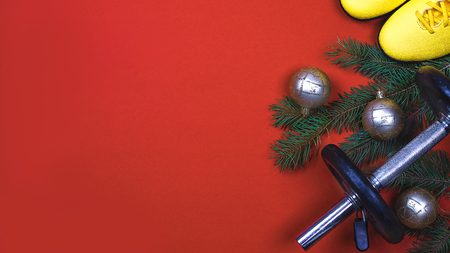Exercise, Fitness, sport and Working Out Merry Christmas and Happy new year background with dumbbells, yellows sneakers, branches fir tree, holiday decorations on red background. Copy space. Flat lay.