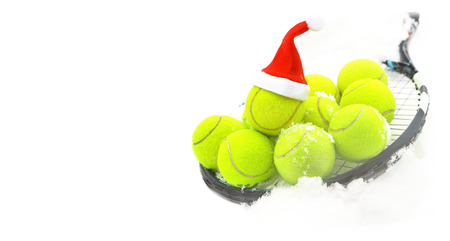 Tennis winter concept with tennis balls and racket on white snow, isolated. Top view, copy space. Christmas New Year sport healthy layout. Santa Claus hat on the top off ball. Banner size.