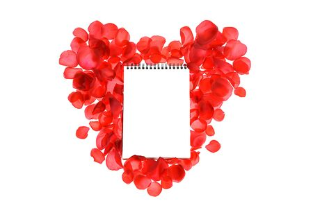 Red coral roses petals on heart shape and notebook isolated on white background. Love concept. Flat lay, top view, copy space. Valentines day, party, wedding, holiday, romance beauty conception.