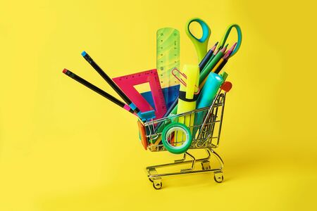 Back to school concept with shopping cart and colorful pencils, square ruler, scissors, clips, markers on pastel yellow backdrop. Flat lay, top view, copy space.