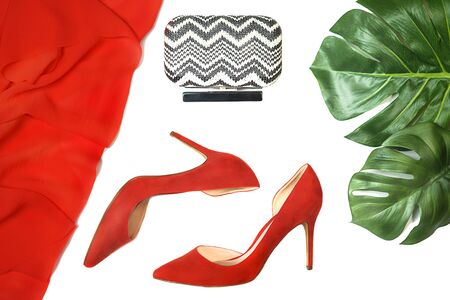Top view party outfit red shoes accessories clutch tropical monstera leaves on white background, isolated. Party Valentines Day Christmas Happy New Year wedding dinner layout. Flat lay, copy space. 스톡 콘텐츠