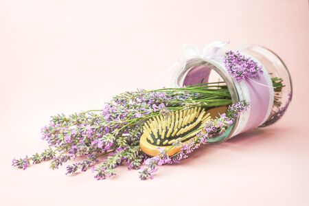Wooden scalp and massage brush and hair comb with lavender flowers on pastel pink background. Toned, close-up, vintage style.